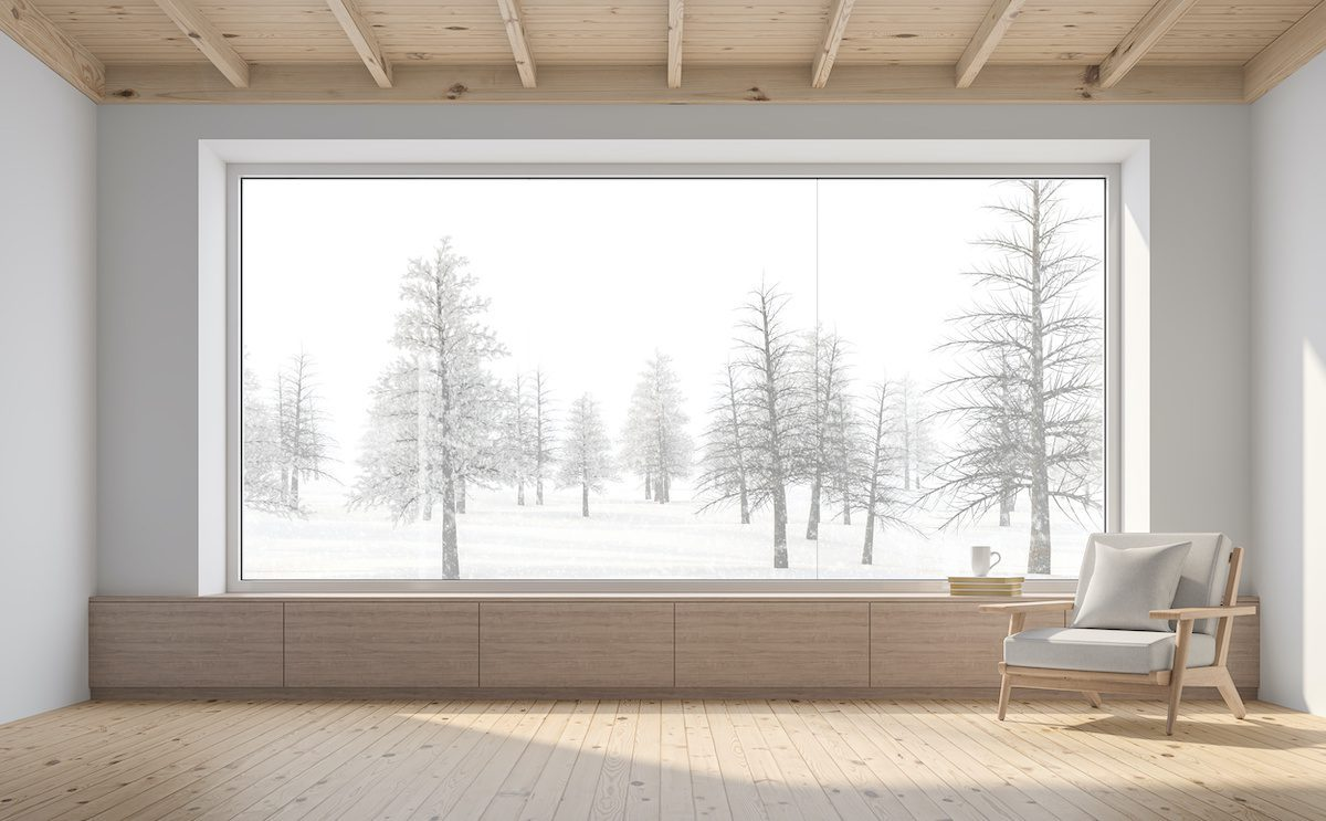 Empty room with large window showing winter forest.
